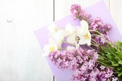 Lilac and white anemone flowers. Branch of lilac and white anemone flowers on wooden background. Concept mother`s day. Copy space. Top view royalty free stock photography