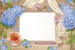 Lilac on wooden background. Spring top view composition with blank sheets of paper, blossoming tree branches, glass teacup and butterfly Royalty Free Stock Photos