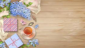 Lilac on wooden background. Spring top view composition with a silk scarf, gifts, blossoming tree branches, glass teacup and butterfly Stock Images