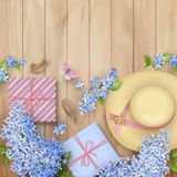 Lilac on wooden background. Spring top view composition with a straw hat, blossoming tree branches, gifts, feathers and butterfly Stock Photography