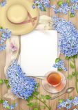 Lilac on wooden background. Spring top view composition with blank sheets of paper, a straw hat, blossoming tree branches, glass teacup and butterfly Stock Photos