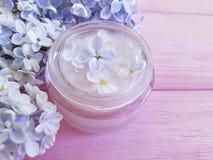 Lilac zorg van de room de kosmetische regeneratie bij het roze houten harmonie bevochtigen stock foto's