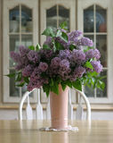 Lilacs. Vase of lilacs on a wooden farm table Royalty Free Stock Photo