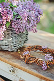 Lilacs in basket and handmade wreath on vintage bureau in spring garden Stock Photography