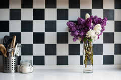 Lilacs in a vase and kitchen utensils Stock Image