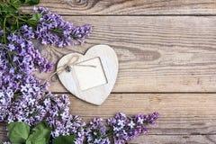 Lilan blommar med dekorativ ram-hjärta på gammal träbackgrou Royaltyfri Foto
