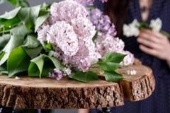 Lilan blommar på ett träsnitt och flicka i bakgrunden Rosa färg-, vit- och lilablommor arkivfoton