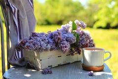 Lilas en una cesta de mimbre con una taza de té Foto de archivo libre de regalías