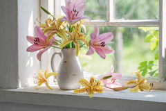 Lilies bouquet on a window sill in sunny  day Royalty Free Stock Photos