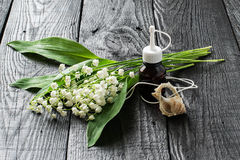 Lilies of the valley and essential oil in vial. Lilies of the valley convallaria majalis and essential oil in vial and aromatic pendant. Aroma of the lily-of-the Stock Photo