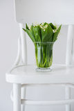 Lilies of the valley in vase on a rustic chair Royalty Free Stock Photography