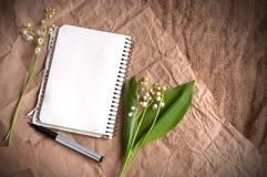 Lilja av dalar, den tomma notepaden och pennor på säckvävtextur arkivbild