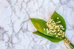 Liljekonvalj eller kunna-lilja på marmorbakgrund arkivfoto