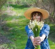 Liljekonvalj i händer av den härliga flickan Royaltyfria Bilder