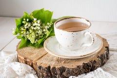 Liljekonvalj och kopp te, stilleben Royaltyfri Bild