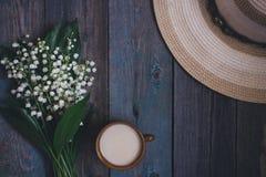 Liljekonvaljbuketten, koppen kaffe, te, mjölkar, på trätabellen fotografering för bildbyråer