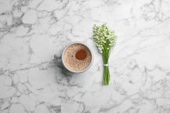 Liljekonvaljbuketten och kaffe marmorerar p? bakgrund royaltyfri fotografi