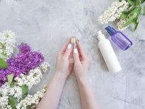 Lill? cosmetico del fiore delle mani del manicure della crema di estate femminile dell'estratto su fondo concreto grigio immagine stock libera da diritti