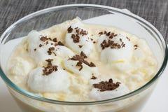 Ägg skummar att sväva på mjölkar smaksatt med vanilj- och citronpeelen Arkivfoton