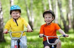 Lilla barn som rider deras cyklar Fotografering för Bildbyråer