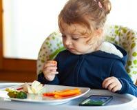 Lilla barnet äter, medan hålla ögonen på filmer på mobiltelefonen arkivfoto