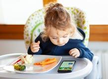 Lilla barnet äter, medan hålla ögonen på filmer på mobiltelefonen royaltyfri bild