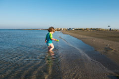 Lilla barnet behandla som ett barn att spela i grunt havsvatten royaltyfri fotografi