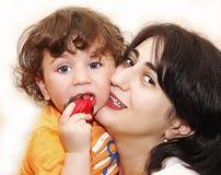 Lilla barnet behandla som ett barn rymma en leksak så långa håll för mamma för blåa ögon för ögonfrans Fotografering för Bildbyråer