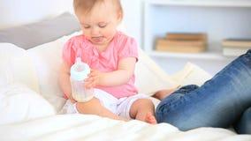 Lilla barnet som spelar med hennes, behandla som ett barn flaskan stock video