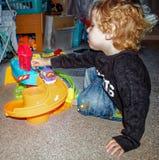 Lilla barnet som spelar med leksakbilar, och leksaken parkera bilen i garage Arkivfoton