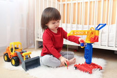 Lilla barnet spelar bilar Arkivfoton