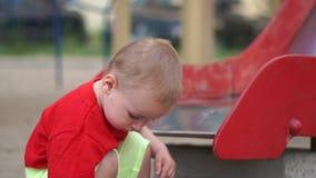 Lilla barnet squatting nära glidbanan i lekplatsen och spelar i ultrarapid arkivfilmer