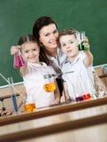 Lilla elever lärer kemi royaltyfria foton