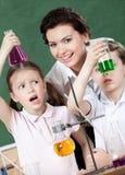 Lilla elever undrar på resultatet av experiment Arkivbild