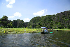 Lilla fartyg som seglar för att se ricefält på Tam Coc Royaltyfri Fotografi