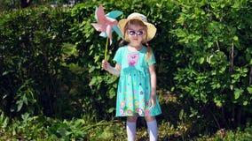 Lilla flickan är den hållande lilla solen på bakgrund av gröna buskar i sommar stock video