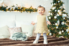 Lilla flickan är en hare på bakgrundsträden glad jul Arkivfoto
