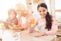 Lilla flickan är hållande exponeringsglas av orange fruktsaft, medan sitta med hennes farmor och broder i kök arkivbilder
