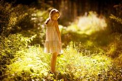Lilla flickan är i en skog Royaltyfri Bild