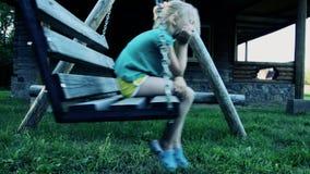 Lilla flickan är uppriven på gungorna anstöt stock video