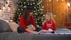 Lilla flickan äter godisen med modern nära julgranen arkivfilmer