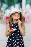 Lilla flickan äter jordgubben arkivbild