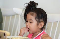Lilla flickan äter läcker mat royaltyfri bild