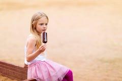 Lilla flickan äter pajen för eskimo för pinneglassstången fotografering för bildbyråer