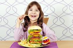 Lilla flickan äter stora hamburgare- och fransmansmåfiskar Fotografering för Bildbyråer