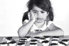 Lilla flickan önskar att äta massor av chokladkakor Arkivbilder