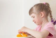 Lilla flickan önskar inte att äta en apelsin royaltyfria bilder