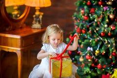 Lilla flickan öppnar en gåva Arkivfoto