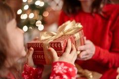 Lilla flickan överför hennes moder en julgåva Fotografering för Bildbyråer