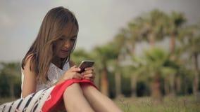 Lilla flickan använder en smartphone på en grön gräsmatta med palmträd stock video